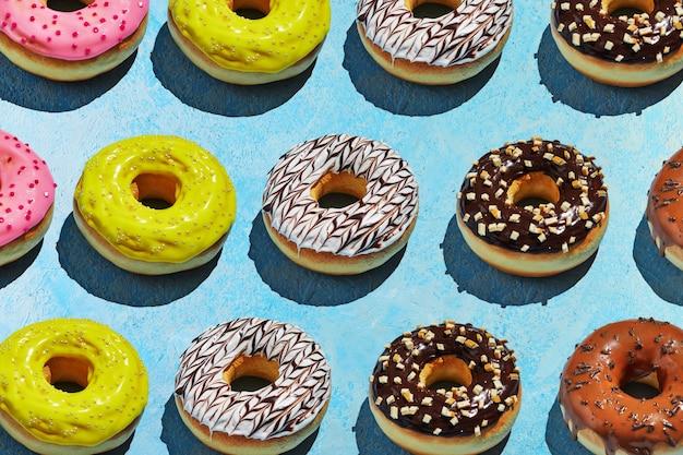 Donuts muster mit weißer, gelber und brauner glasur auf einem blauen hintergrund.