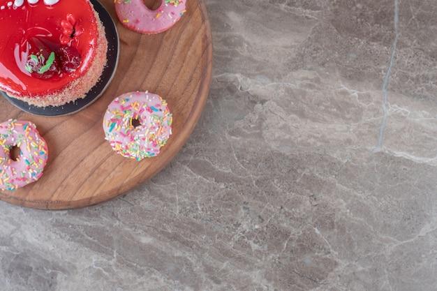 Donuts um einen mit erdbeersirup belegten kuchen auf einem brett auf marmoroberfläche