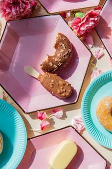 Donuts und eis auf tellern mit dianthusblättern