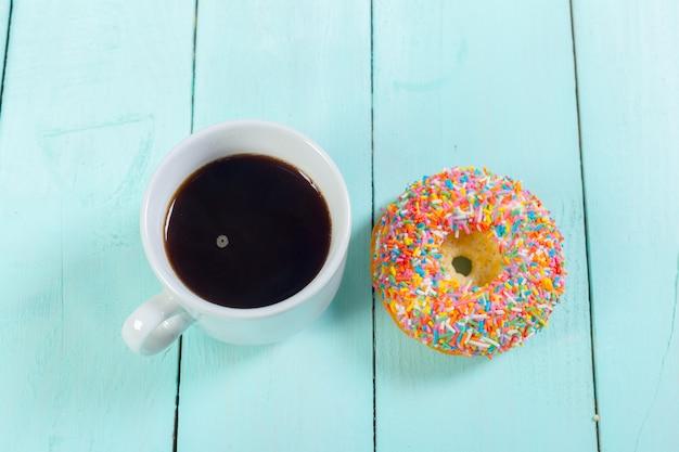 Donuts und kaffee auf holztisch. ansicht von oben