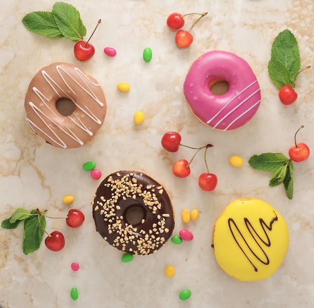 Donuts und kirschen, minzblätter auf marmor
