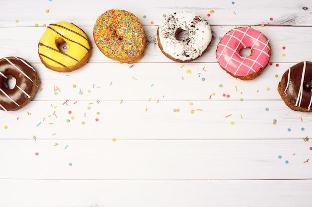 Donuts und konfetti auf einem holztisch mit platz für ihren text.