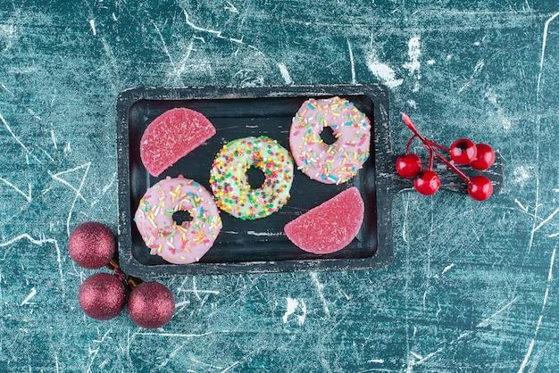Donuts und marmeladen auf einer kleinen platte neben weihnachtskugeln auf blau.