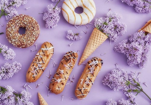 Donuts und sahnetorten liegen auf dem tisch zwischen lila blumen auf lila papier. frühling und süßigkeiten, leckere kuchen. stillleben und sommerstimmung, ansicht von oben. donuts