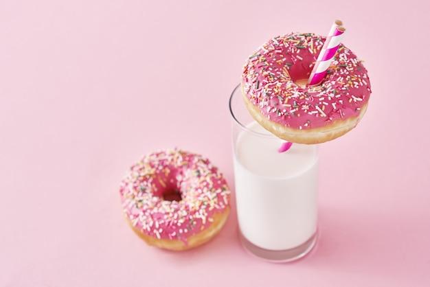 Donuts verziert mit zuckerguss und streusel und glas milch auf rosa hintergrund