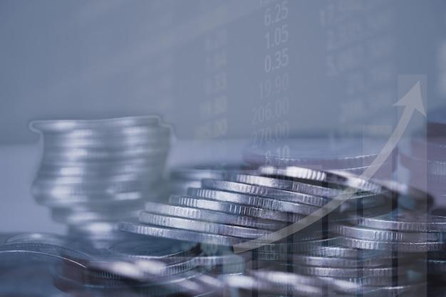 Doppelbelichtung des münzenstapels mit börseenschirm-diagrammbrett