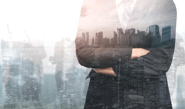 Doppelbelichtungsbild der geschäftsperson auf der modernen stadt. zukünftiges geschäfts- und kommunikationstechnologiekonzept.