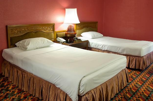 Doppelbett mit tischlampe im schlafzimmer in der nacht