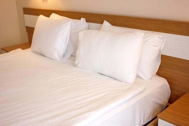 Doppelbett mit weißer bettwäsche, zum schlafen vorbereitet