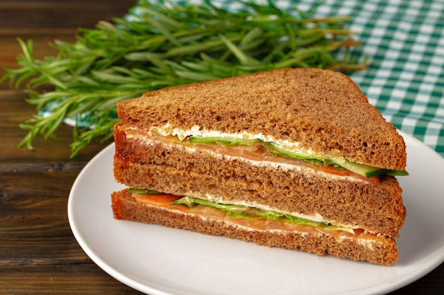 Doppelklub-sandwich auf teller auf holztisch serviert