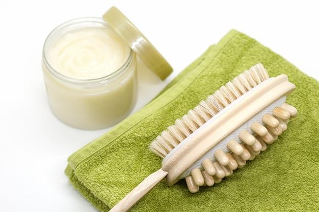 Doppelseitige massagebürste zum bürsten des körpers liegt auf dem handtuch auf dem hintergrundkörperpeeling