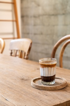 Doppelte schmutzige kaffeetasse (espresso mit milch und schokolade) im café