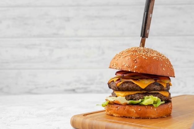 Doppelter cheeseburger auf holzbrett vor weißem hintergrund unscharf serviert