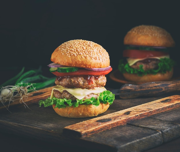 Doppelter cheeseburger in einem brötchen mit samen des indischen sesams