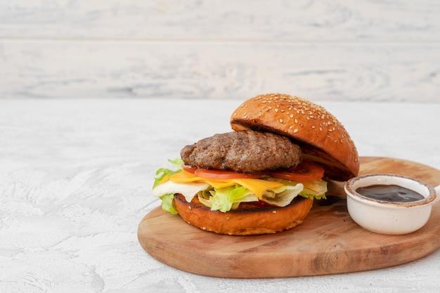 Doppelter cheeseburger serviert auf holzbrett vor weißem unscharfem hintergrund