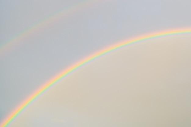 Doppelter regenbogen am himmel. nach dem regen. naturwunder. bewölkter himmel auf einem regenbogenhintergrund. ein symbol des friedens. und lgbt