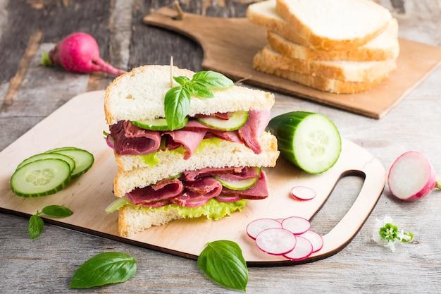 Doppeltes sandwich mit pastrami und frischem gemüse und kräutern auf einem schneidebrett. amerikanischer imbiss. rustikaler stil.