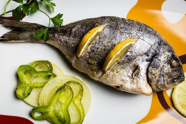 Dorada-fische, die im ofen mit zitrone, piment und frühlingszwiebel gekocht wurden, dienten auf einem behälter auf einem holztisch
