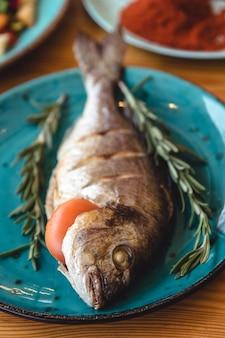 Dorado mit frischem fisch. dorado und zutaten zum kochen auf einem tisch.
