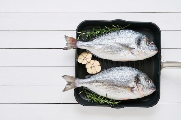 Dorado mit zwei rohen seebrassenfischen mit gewürzen in einer pfanne auf dem weißen holztisch