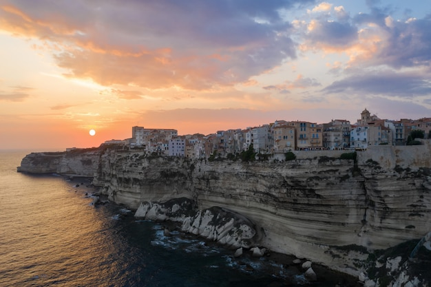 Dorf auf einer klippe über dem ozean bei sonnenuntergang