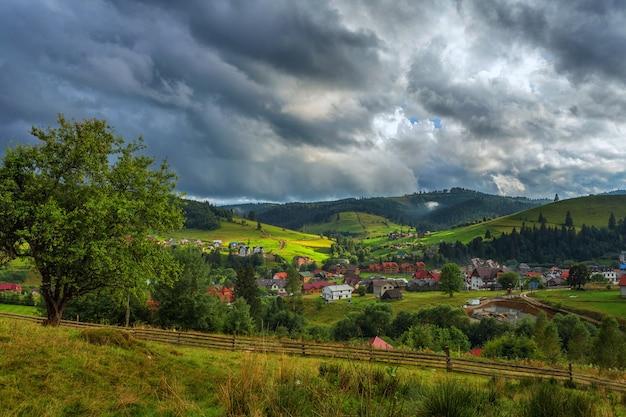 Dorf in den bergen, vor dem hintergrund der grünen hänge und der wälder, himmel mit gewitterwolken