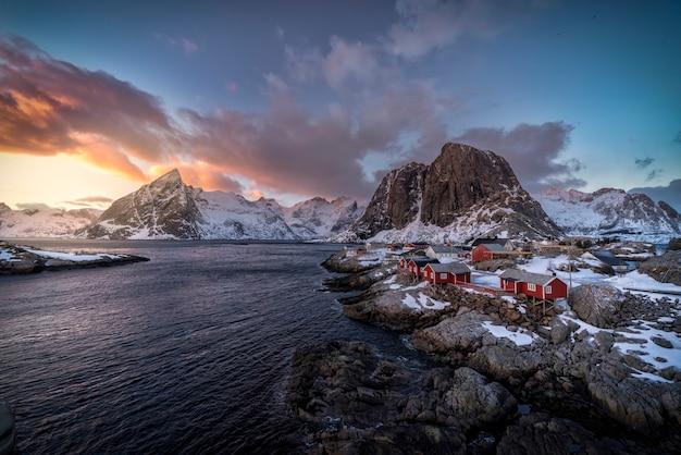 Dorf mit roten hütten durch das meer mit bergen im hintergrund bedeckt im schnee im sonnenuntergang in den lofoten-inseln, norwegen