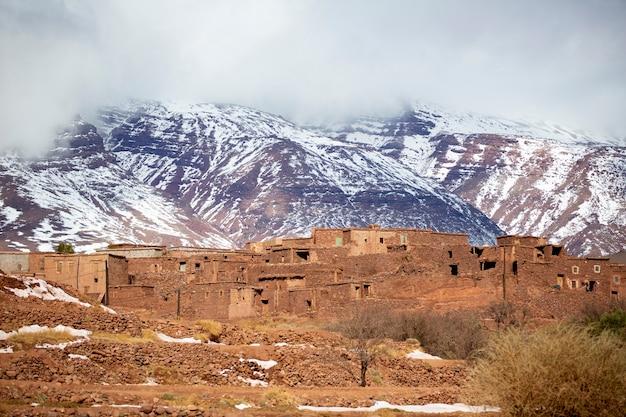 Dorf mit schneebedecktem atlasgebirge im rücken in marokko