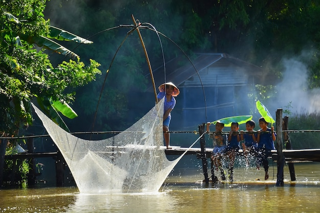 Dorfbewohner und kinder tun traditionelles thailändisches traditionelles fischen im fluss. in chiang mai, thailand 05.12.2021