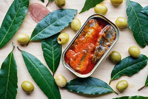 Dose tomatensardinen von oben mit oliven und lorbeerblättern