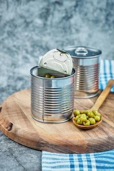 Dosen gekochter grüner erbsen mit holzbrett und löffel.