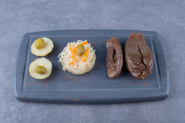Dosen gemüse. sauerkraut und gefüllte aubergine auf holzbrett.