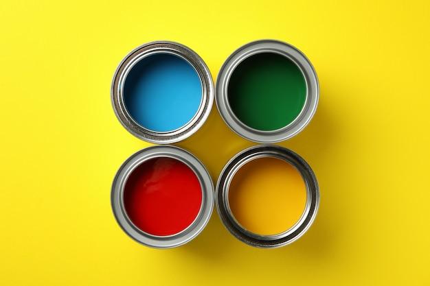 Dosen mit unterschiedlicher farbe auf gelbem hintergrund, draufsicht