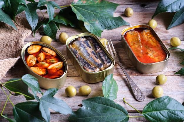 Dosen sardinen in öl und mit tomate und eine weitere dose muscheln auf einem rustikalen holztisch