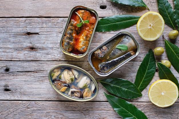Dosen sardinen mit öl, tomaten und muscheln auf rustikalem holz.