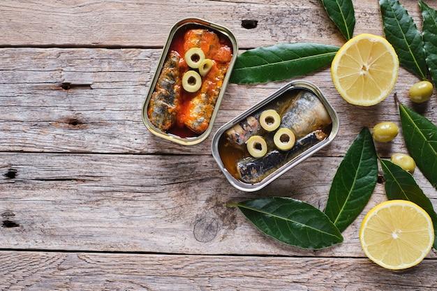 Dosen sardinen mit öl und tomaten auf rustikalem holz.