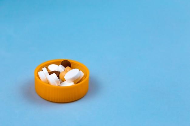 Dosis der farbigen pillen in der kappe der pillenpackung. auf blauem hintergrund