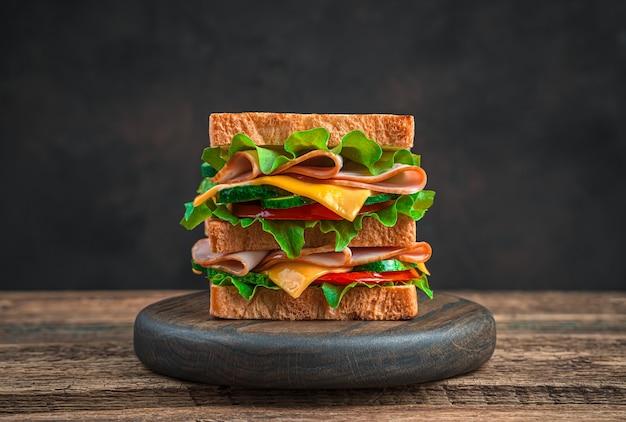 Double club sandwich mit käse, schinken, tomate und gurke auf braunem hintergrund. seitenansicht, nahaufnahme. fast food.