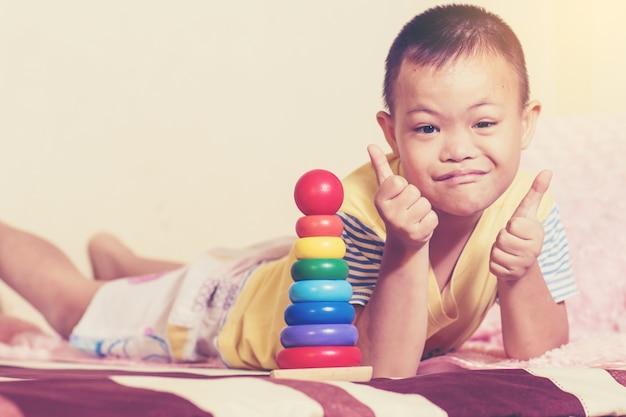 Down-syndrom junge zeigen zwei daumen hoch, wenn er frage farbe holzspielzeug zu vervollständigen