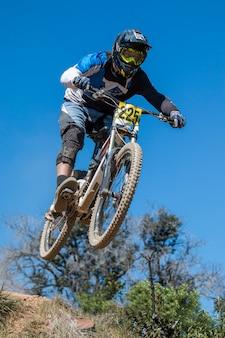 Downhill-wettkampf, biker springt schnell ins grüne.