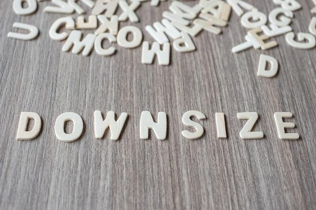Downsize-wort von buchstaben des hölzernen alphabets. geschäfts- und ideenkonzept