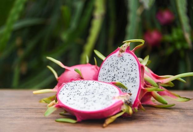 Drachefruchtscheibe auf hölzernem mit dracheobstbaum - konzept der tropischen frucht des neuen pitaya sommers