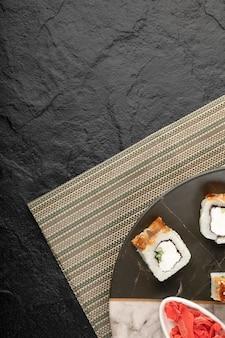 Drachen-sushi-rollen mit aal und eingelegtem ingwer auf marmorplatte