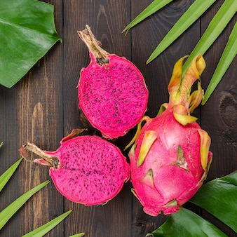 Drachenfrucht auf den blättern von palm und monster