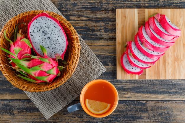 Drachenfrucht in einem korb mit tischset, tee flach lag auf holz und schneidebrett