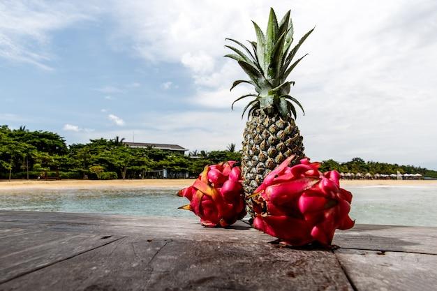 Drachenfrucht und ananas an einem exotischen strand.