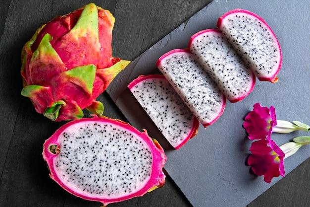 Drachenfruchtscheiben mit blüten auf stein- und holzbasis pitaya-tropenfrucht