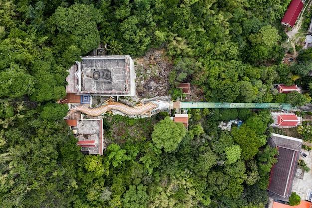 Drachestatue mit tempel und rotem schrein auf hügel im tropischen regenwald bei wat ban tham