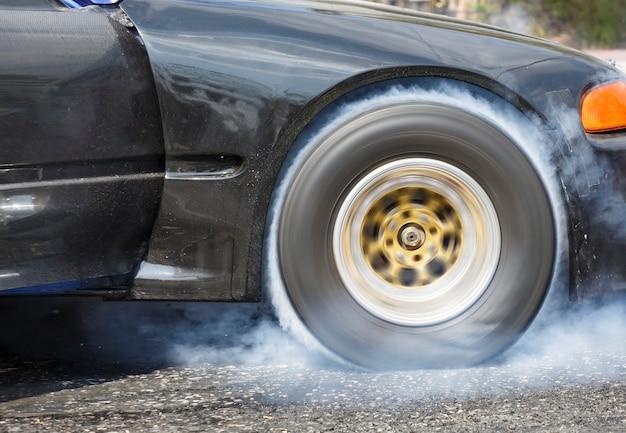 Drag racing-wagen verbrennt gummi von seinen reifen, um sich auf das rennen vorzubereiten