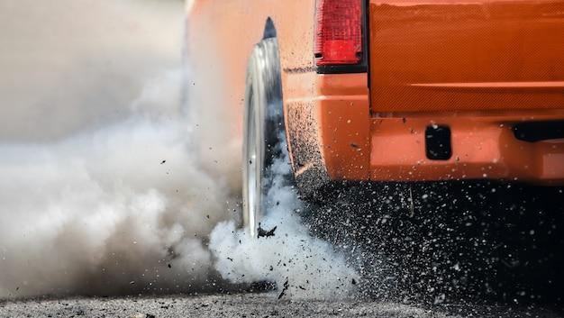 Drag-rennwagen brennt in vorbereitung auf das rennen gummi von den reifen